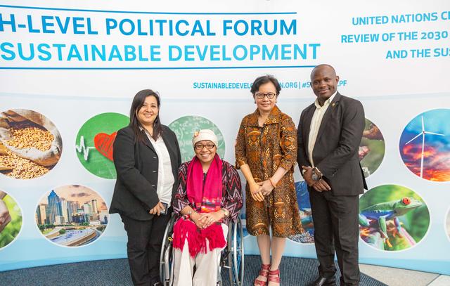 Pratima Gurung, Risna Utami, Maulani Rotinsulu, Ambrose Murangira in front of Sustainable Development banner