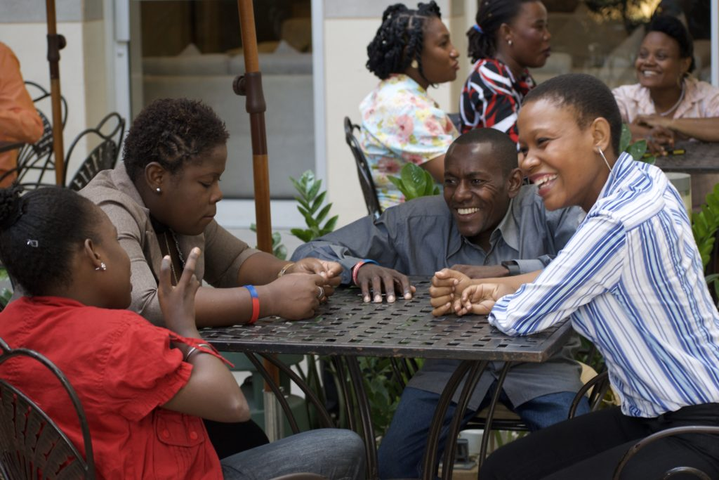 Haitian grantees sit around a small table while one person speaks and the others are smiling as they listen.