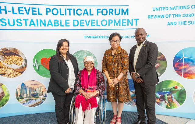 Pratima Gurung, Risna Utami, Maulani Rotinsulu, Ambrose Murangira in front of Sustainable Development banner