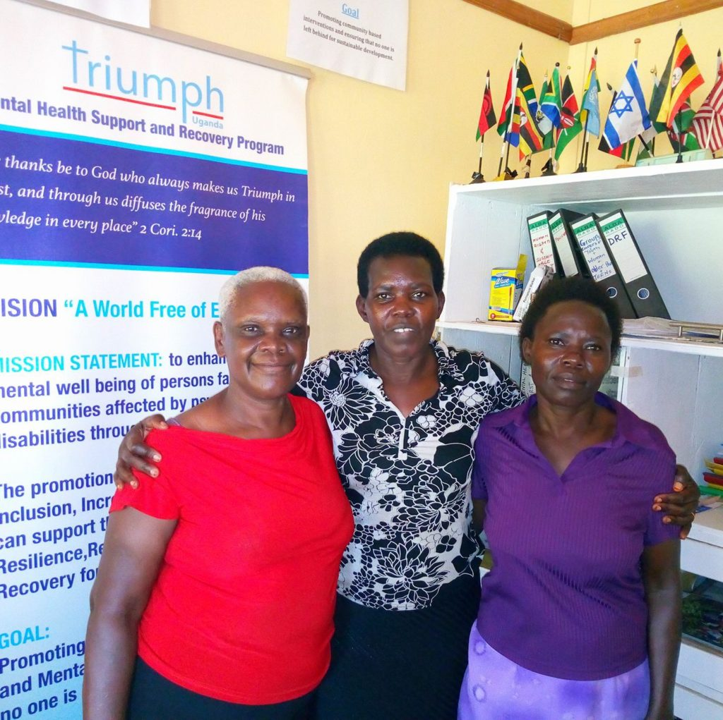 three ugandan woman stand next to a sign for Triumph Uganda