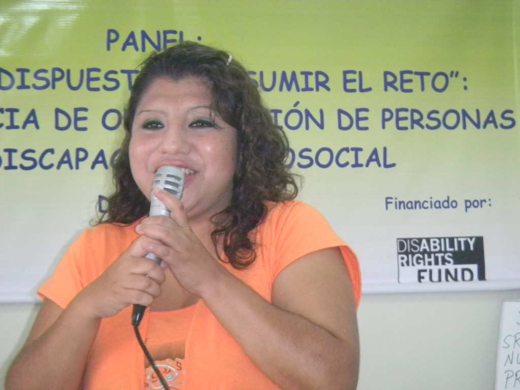 Woman with dark curly hair wearing orange top speaks in to a microphone