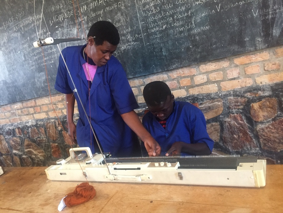 A teacher shows a student with a visual impairment how to use a machine
