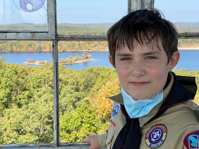 Sebastian, a 12 year old boy, looks at the camera smiling with his face mask pulled down. He is standing in front of a window that looks out over water and trees.