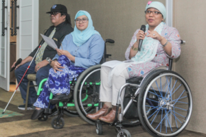 Lady in wheelchair speaking into microphone.